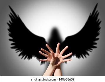 Angel, hand shadow like wings of darkness