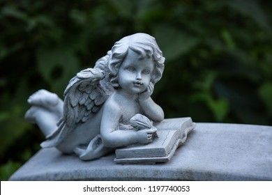 An angel lies on his belly and writes with a feather in a book