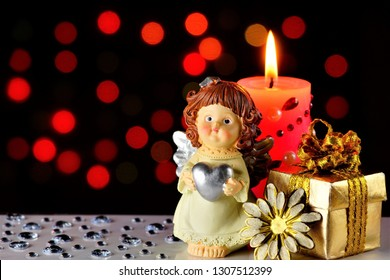 The angel of love, a gift, a pink candle, and a festive background with hearts and bright lights. Valentine's day, the Winged angel of love communicates the will of God and has supernatural powers.