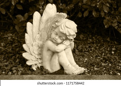 angel made of clay sitting in a hedge on a grave - sepia colored