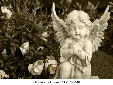 angel made of clay sitting on a grave surrounded by flowers - sepia colored