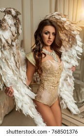 Angel muse in th white interior curly pretty woman with big white gold wings