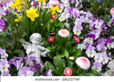 Angel on a grave with spring flowers