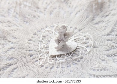 angel on paper heart on lace napkin. soft focus