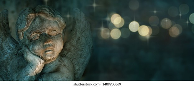 Angel sculpture with golden bokeh on dark background