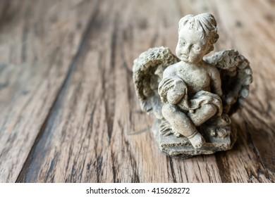 angel sculpture on wooden background