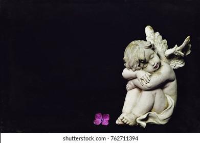 Angel sleeping on dark background