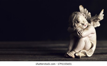 Angel sleeping on dark wooden background with copy space