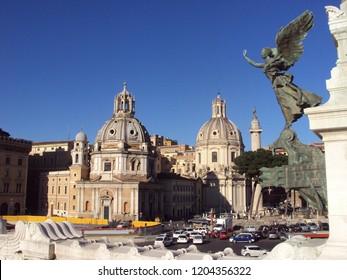 Angel statue at Altare della Patria, Rome. In the background, the Santissimo Nome di Maria al Foro Traiano Church