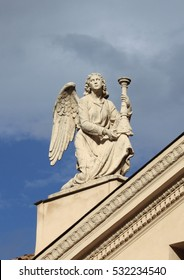 Angel statue with candelabra on top of Saint Rocco church in Rome, Italy
