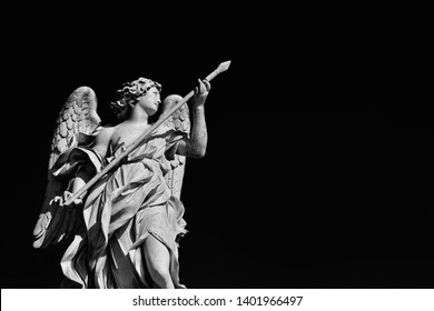Angel statue holding the Holy Lance of Longinus A 17th century baroque masterpiece at the top of Sant'Angelo Bridge in the center of Rome  (Black and White with copy space)