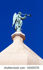 Angel statue on top of a dome, in front of a blue sky background. Detail of the Cathedral of Virgin Mary's Assumption. Island Krk, Croatia