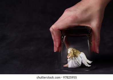 An angel trapped under a glass, a child angel or fallen angel