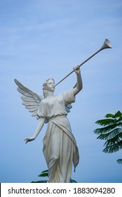 an angel with trumpet with blue sky as background