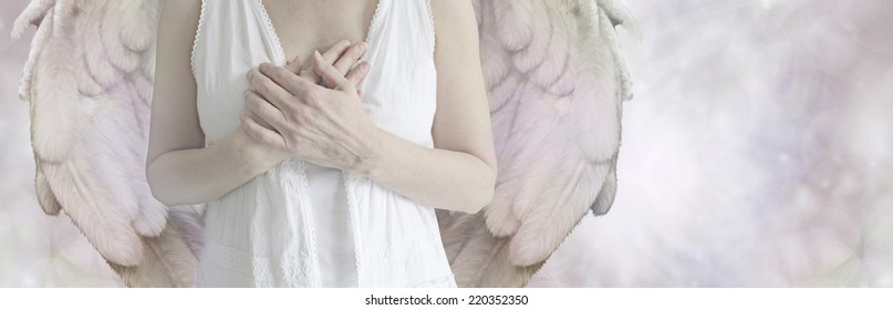 Angel Website Banner  -  Cropped Angel showing torso in white robes with hands held over heart on a misty bokeh background with copy space on right hand side