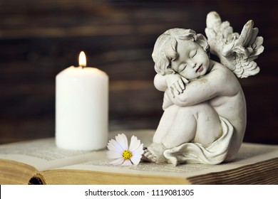 Angel, white candle and flower on the book