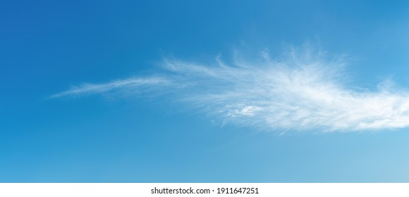 Angel wing shaped cloud against azure heaven. White cloud like a swan wing high in a blue sky. Translucent cirrus spindrift clouds high up. Purity and serenity concepts. Panoramic skyscape shot. - Shutterstock ID 1911647251
