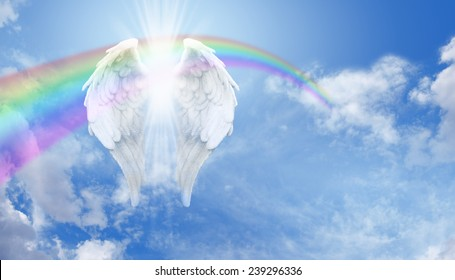 Angel Wings - Floating Angel wings with an arcing rainbow and bright sunburst behind on a blue sky background with plenty of copy space on the right hand side