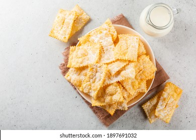 Angel wings - traditional sweet crisp pastry,  deep-fried and sprinkled with powdered sugar,  and milk. Light grey background. Copy space. Top view.