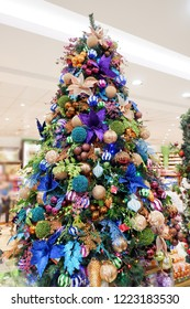 ANGELES, PHILIPINES - 27 OCTOBER 2018: Christmas trees decorated with colorful ornaments indoor isolated