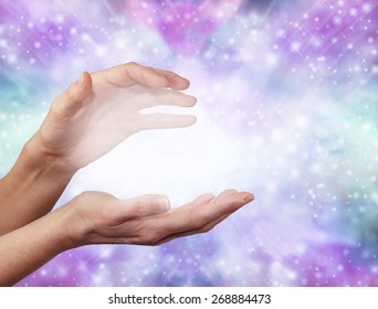 Angelic ethereal healing energy - Female hands in energy sensing position with a ball of white misty light between on a sparkling blue and purple colored background