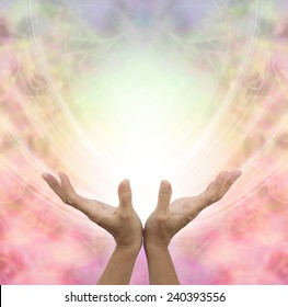 Angelic Healing Energy -  Female hands outstretched sensing a beautiful pastel colored Angelic energy field with a ball of white light at the center and plenty of copy space around