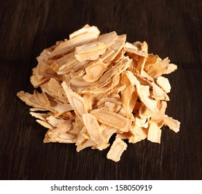 Angelica root slices isolated on a dark brown wooden background