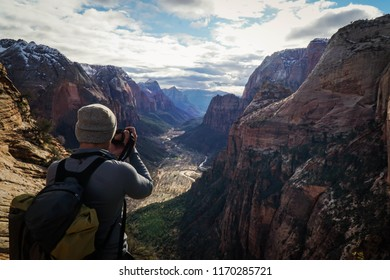 Angels landing hike in Zion.  Adventure hiker capturing the mountain background.  Photographer at work.