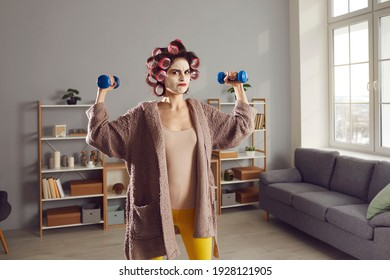 Anger is best motivator. Funny angry woman having sports workout at home. Determined housewife in homewear, curlers and beauty skincare face mask doing fitness exercise with dumbbells in living-room