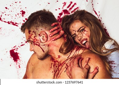 Anger. Passionate anger couple with blood on face. Vampire anger girl bites a muscular man by the neck. Evil and anger woman. Halloween party and holiday. Horror story