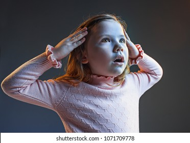 The anger and surprised teen girl. Hate, rage. Crying emotional angry teenager in colorful bright lights at studio background. Emotional face. Sport fan human emotions, facial expression concept.