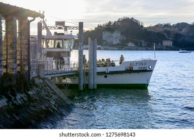 ANGERA, ITALY - DECEMBER 30: bright sun lightens docking station and prow of passenger vessel  at historical touristic village on Verbano lake, shot in winter light on dec 30, 2018 at Angera, Italy
