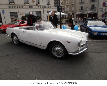 Angers, France - April 7th 2013 : Vintage cars exhibition on the castle parking. Focus on a white convertible car, maybe a modified Peugeot Pininfarina.