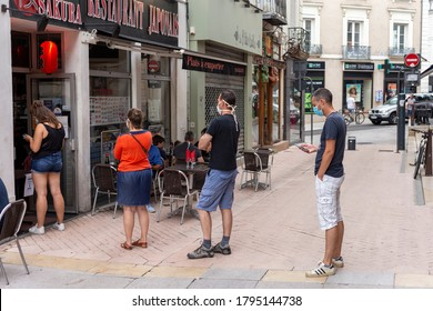 Angers, France - August 11 2020: people wearing face protective mask and keep distance while waiting for a takeout order from a restaurant at France to prevent coronavirus, concept of wearing masks