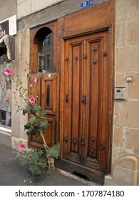Angers, France - September 15th 2012: Focus on a superb wooden door. A hollyhock split the bitumen and pushes ahead.