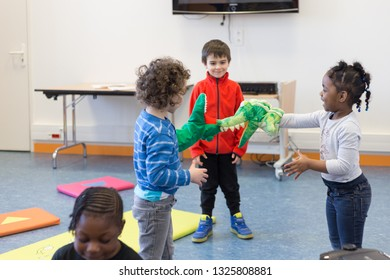 Angers, Maine et Loire / France - February 27 2019: children play dolls, plush crocodiles. three children of different nationalities