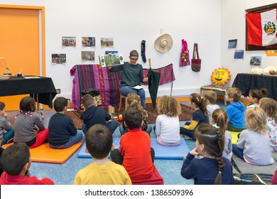 Angers, Maine et Loire/ France - April 24 2019: teacher reading a story to preschool children. thematic lesson about latin america in public library. kids seating on floor and listen.