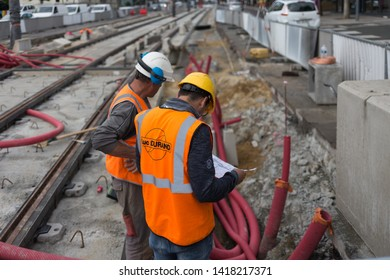 Angers, Maine et Loire / France - June 03 2019: two workers watching plan for job, uniform, orange gilets, white helmets, ears protection, rail grill assembly, evolution maintenance, repair railway