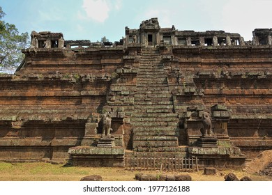 Angkor. An ancient temple in the form of a stepped pyramid with a staircase. At the top there is a dilapidated gallery, a colonnade. At the entrance there are statues of mythical lions. Cambodia