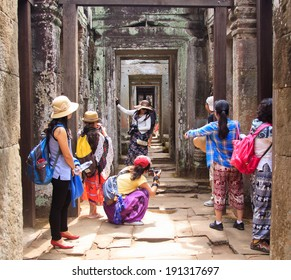 ANGKOR, CAMBODIA - APR 6: Visitors standing at ancient gates of Preah Khan temple, Siem Reap, Cambodia. On April 6, 2014.