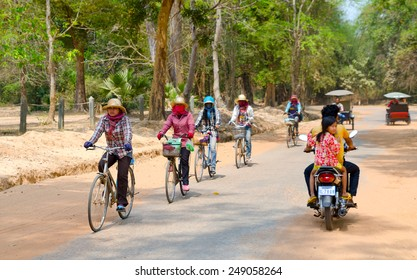 ANGKOR, CAMBODIA - FEB 21, 2013: Unidentified local women and other people ride bicycles and motorbikes at Angkor complex, the prime countrys attraction for tourists.