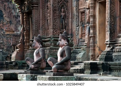 Angkor Cambodia, Monkey guardians sitting at entrance the sanctuary to the 10th century Banteay Srei temple with ornate carved wall in background