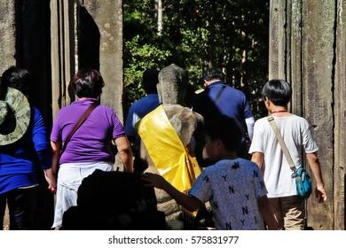 Angkor, Siem Reap, Cambodia - January 9, 2017 - Buddha statue at a facade of Bayon in Angkor Thom (Great City)