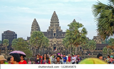 ANGKOR WAT, CAMBODIA, APRIL 2017: Masses of Asian tourists occupy wide walkway leading towards the Angkor Wat entrance. Hordes of people taking photos and selfies in front of ancient Buddhist temples.