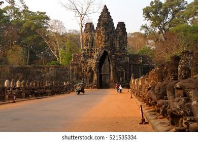 ANGKOR WAT, CAMBODIA - FEB 13, 2015 - Motorbikes and Tuk tuks leave through the gate of Angkor Thom,  Cambodia