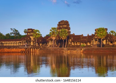Angkor Wat, in Cambodia. General view of western outer gate at sunset with reflections. Angkor Wat is the largest religious monument in the world, and has been declared World Heritage by UNESCO.