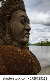 Angkor Wat, Cambodia - June 23, 2016: A statue stands next to a lake at Angkor Wat.