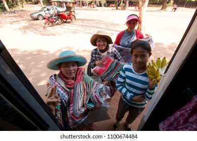 ANGKOR WAT, CAMBODIA, MARCH 2018; Cheerful hawkers approach doors of a tourist bus. Tourism is the second largest sector of Cambodia's economy, according to the OECD.
