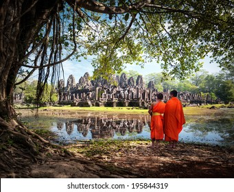 Angkor Wat monk. Ta Prohm Khmer ancient Buddhist temple in jungle forest. Famous landmark, place of worship and popular tourist travel destination in Asia