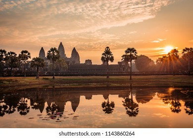 Angkor Wat on a brilliant orange sunrise with a sunstar shining through the trees. The temple and sun a elegantly reflected in one of the pools